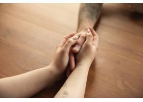 一对恩爱的夫妇在木桌上近距离手牵手_13565396