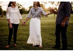 一群朋友在公园里手牵手祈祷_9077329