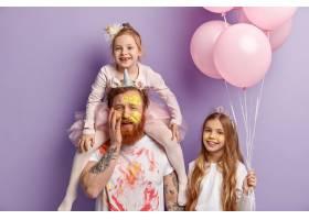 三个家庭成员在室内紫色墙上摆姿势有趣的_11578970