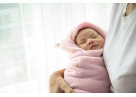 新生婴儿睡在母亲的怀抱里_5897164