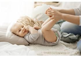 新生的小儿子躺在床上与母亲玩耍的特写照片_8811578