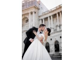 新郎和新娘在历史建筑前接吻前的垂直结婚照_7497136