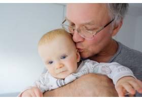 爷爷抱在怀里亲吻可爱的蓝眼睛宝宝特写_9649722