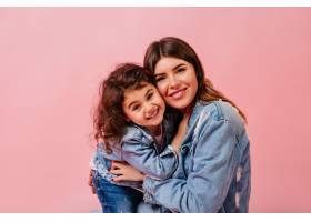 笑着的母女俩看着摄像机粉红色背景上的年_12431977