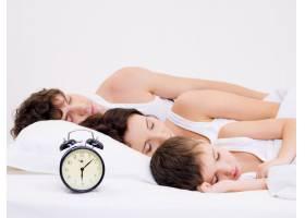 这个年轻的家庭中有三个人头边放着闹钟睡觉_12264587