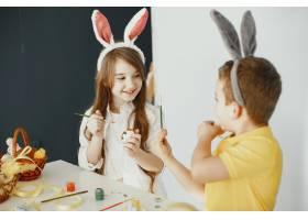 长着兔耳朵的孩子彩绘的复活节彩蛋拿着_13273610