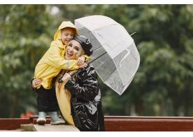 雨天公园里的一家人穿黄色雨衣的孩子和穿_11154985