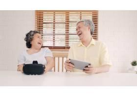 亚洲老年夫妇在起居室里使用平板电脑和虚拟_4396360