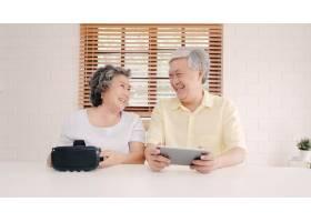 亚洲老年夫妇在起居室里使用平板电脑和虚拟_4396361