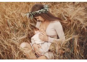 优雅的母亲带着可爱的小女儿在田野里_5557879