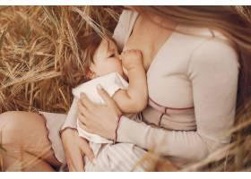 优雅的母亲带着可爱的小女儿在田野里_5557880