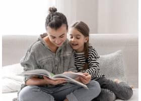 兴高采烈的母女俩正在家里休息一起看书_13333882