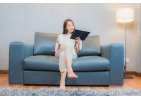 写真美丽的亚洲年轻女子在起居室内的沙发上_10473457