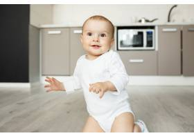 坐在厨房地板上微笑的可爱宝宝_9696758