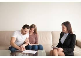 坐在妻子和房地产经纪人旁边的年轻男子签署_3938438