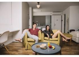 坐在扶手椅上的年轻夫妇看电视_3434711