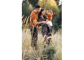 一家人带着他们的小女儿在秋天的田野里_5915972
