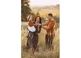 一家人带着他们的小女儿在秋天的田野里_5915976