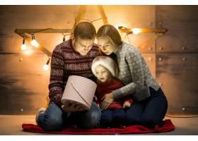 一家人带着小女儿坐在圣诞树旁打包礼物_1472654