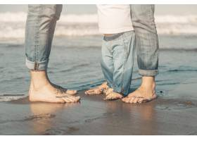 一家人站在海边的沙滩上_4360520