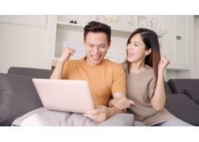 一对亚洲夫妇在家中的起居室里使用笔记本电_4015322