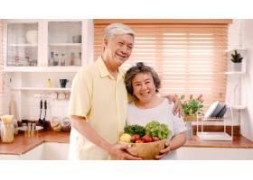 一对亚洲老年夫妇在家中的厨房里放松的同时_4396425