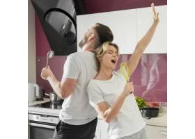 一对在室内一起在厨房唱歌的夫妇_9010383