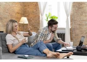 一对夫妇在家中与家人进行视频通话_13453460