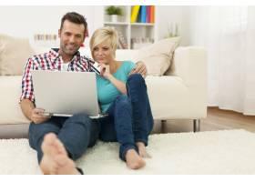 一对夫妇坐在家里的地毯上在网上购物_10675095
