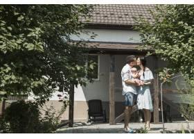 一对夫妇抱着孩子在家前接吻_3279910