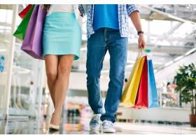 一对提着购物袋沿着商场散步的夫妇_856896