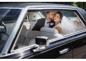 一对新人正坐在汽车的后座上接吻_7497110