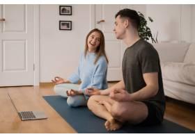 一对漂亮的夫妇在家中用笔记本电脑一起练习_13417886