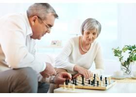 一对老年夫妇在家中玩国际象棋_858655
