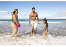 一对家庭夫妇和小女孩在深至脚踝的海水中行_10607986