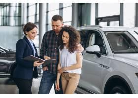 一对年轻夫妇在汽车展厅与销售人员交谈_5157714