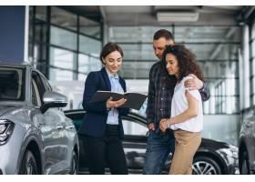 一对年轻夫妇在汽车展厅与销售人员交谈_5157715