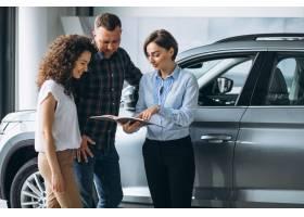 一对年轻夫妇在汽车展厅与销售人员交谈_5177618