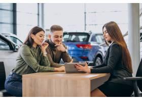 一对年轻夫妇在汽车展厅与销售人员交谈_7200771