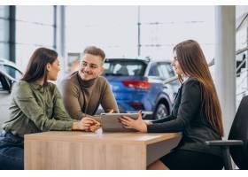 一对年轻夫妇在汽车展厅与销售人员交谈_7200772