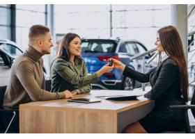 一对年轻夫妇在汽车展厅与销售人员交谈_7200775