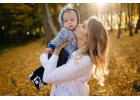 一对年轻夫妇带着一个小男孩走在树林里_3280609