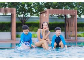 肖像美丽的亚洲年轻女子与儿子在游泳池边享_9873883