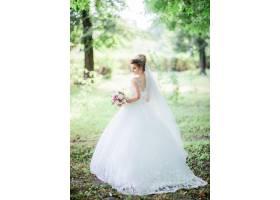 迷人的新娘在公园里拿着五颜六色的结婚花束_2612792