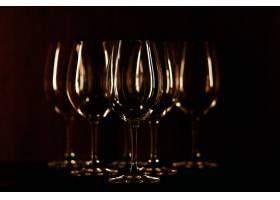 暖光照亮的酒杯矗立在黑色背景上_1612731
