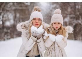 母亲和女儿一起在冬季公园散步_3964098
