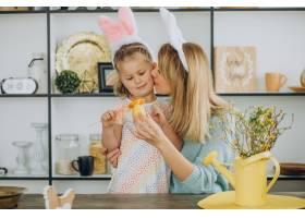 母亲和女儿一起在厨房里拿着复活节彩蛋_13376894