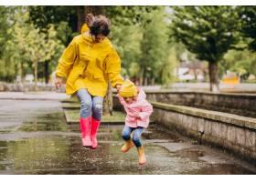 母亲和女儿在水坑里跳得很开心_8828093