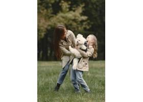 母亲和女儿在玩狗秋天公园的一家人宠物_11191157
