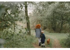母亲和女儿在玩狗秋天公园的一家人宠物_11193257
